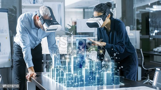 istock Male and Female Architects Wearing  Augmented Reality Headsets Work with 3D City Model. High Tech Office Professional People Use Virtual Reality Modeling Software Application. 921019710
