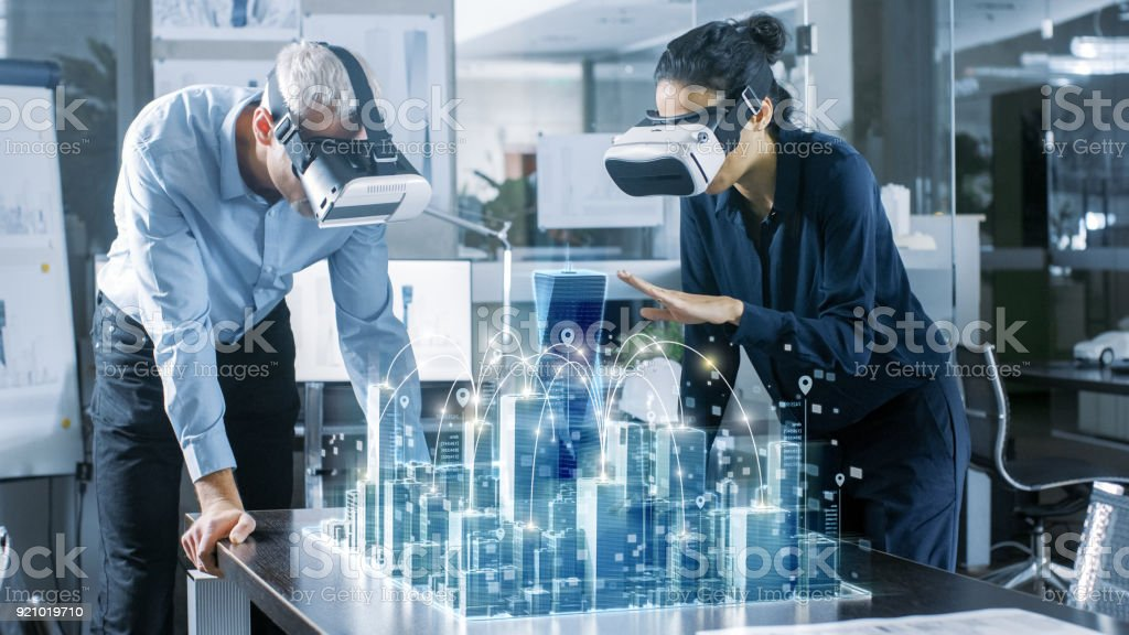 Mannelijke en vrouwelijke architecten dragen Augmented Reality Headsets werken met 3D-City-Model. High Tech Office professionele mensen gebruik Virtual Reality Modeling Software-applicatie.​​​ foto