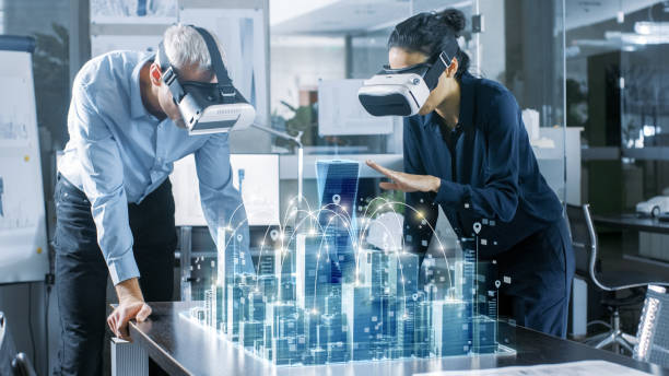 male and female architects wearing  augmented reality headsets work with 3d city model. high tech office professional people use virtual reality modeling software application. - futuristic technology imagens e fotografias de stock