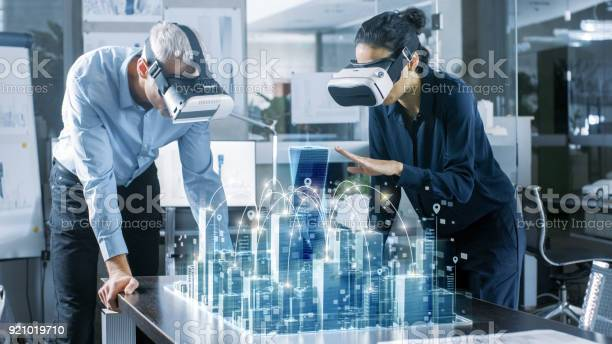 Male And Female Architects Wearing Augmented Reality Headsets Work With 3d City Model High Tech Office Professional People Use Virtual Reality Modeling Software Application Stock Photo - Download Image Now