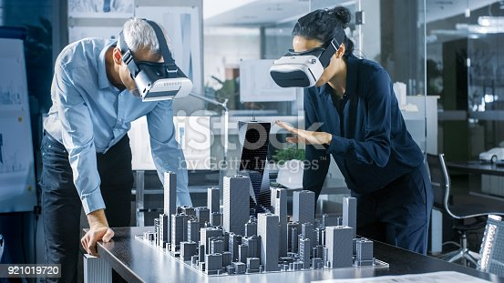 istock Male and Female Architects Wearing  Augmented Reality Headsets Work with 3D City Model. High Tech Office Professional People Use Virtual Reality Modeling Software Application. 921019720