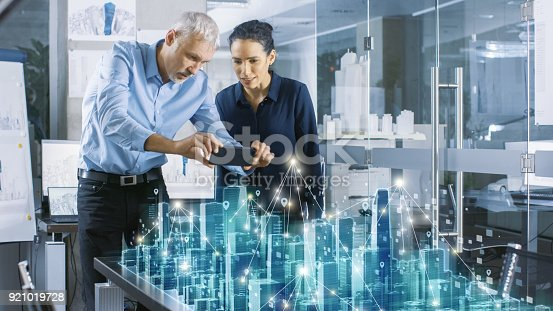 istock Male and Female Architects Work with Holographic Augmented Reality 3D City Model. Technologically Advanced Office Professional People Use Virtual Reality Modeling Software Application. 921019728