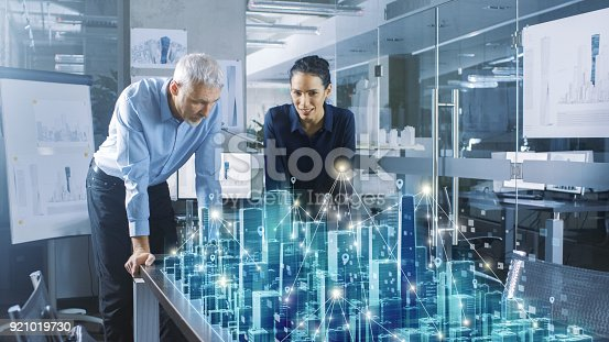 istock Male and Female Architects Work with Holographic Augmented Reality 3D City Model. Technologically Advanced Office Professional People Use Virtual Reality Modeling Software Application. 921019730