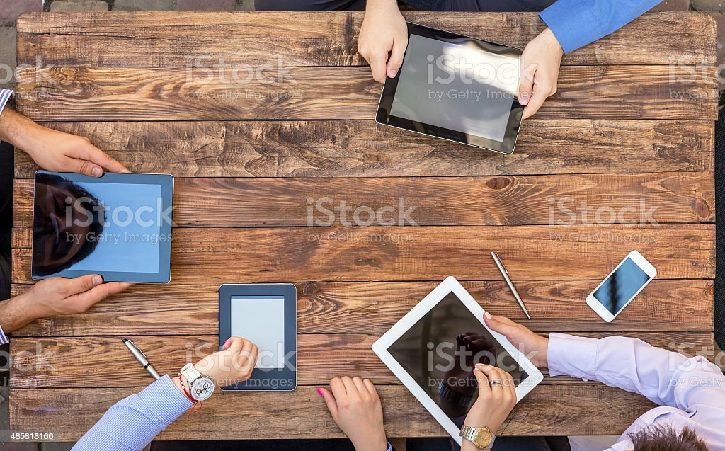 Male and Female Arms with Digital Gadgets stock photo