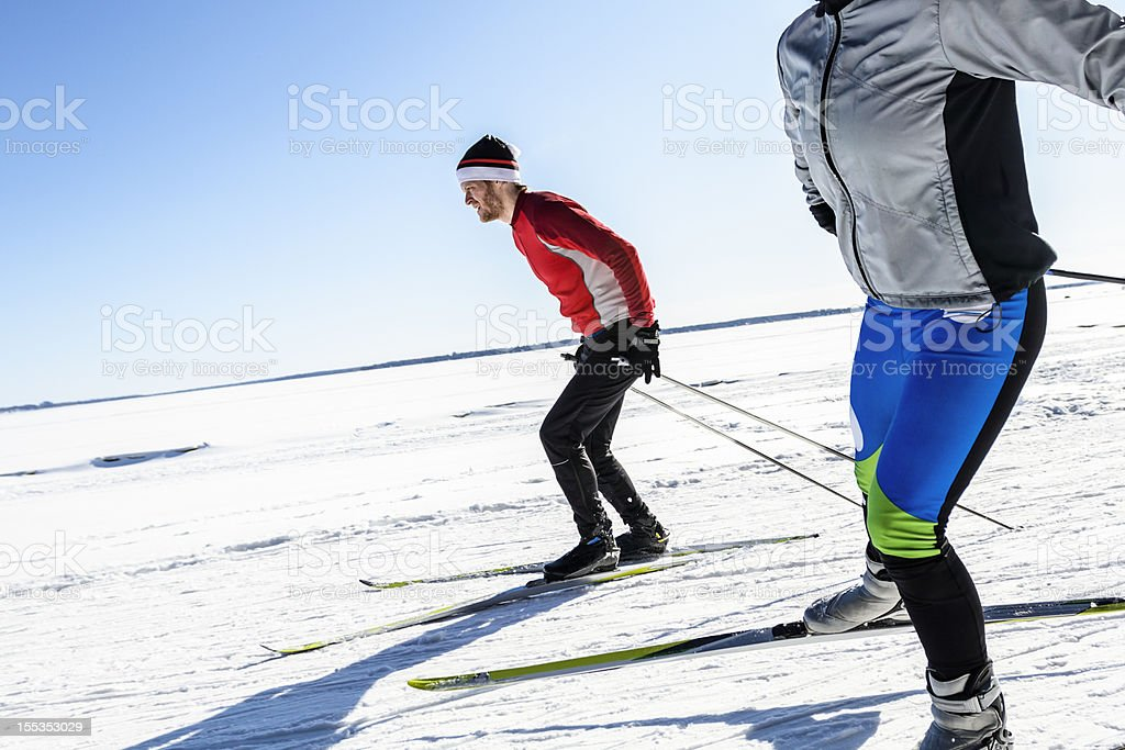 Male and female athletes cross-country skiing. stock photo