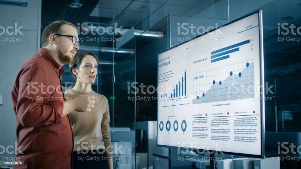 Male and Female Business Coworkers in Conference Room Have Discussion about Statistics and Graphs Shown on a Presentation TV. royalty-free stock photo