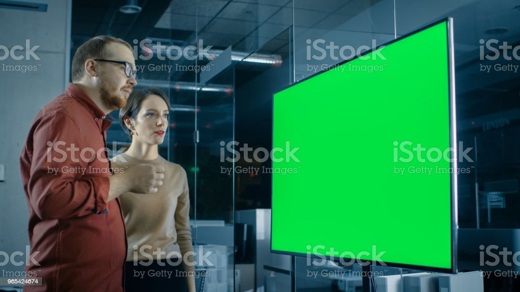 Male and Female Business Coworkers in Conference Room Have Discussion about Green Screen Chroma Key Template Shown on a Presentation TV. zbiór zdjęć royalty-free