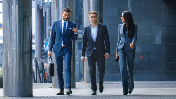 male and female business people walk and discuss business. they're all working in central business district. - bankers stock photos and pictures