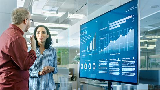 회의실에서 남성과 여성의 비즈니스 노동자 통계 및 프레 젠 테이 션 Tv에 표시 하는 그래프에 대 한 논의가 있다 2명에 대한 스톡 사진 및 기타 이미지
