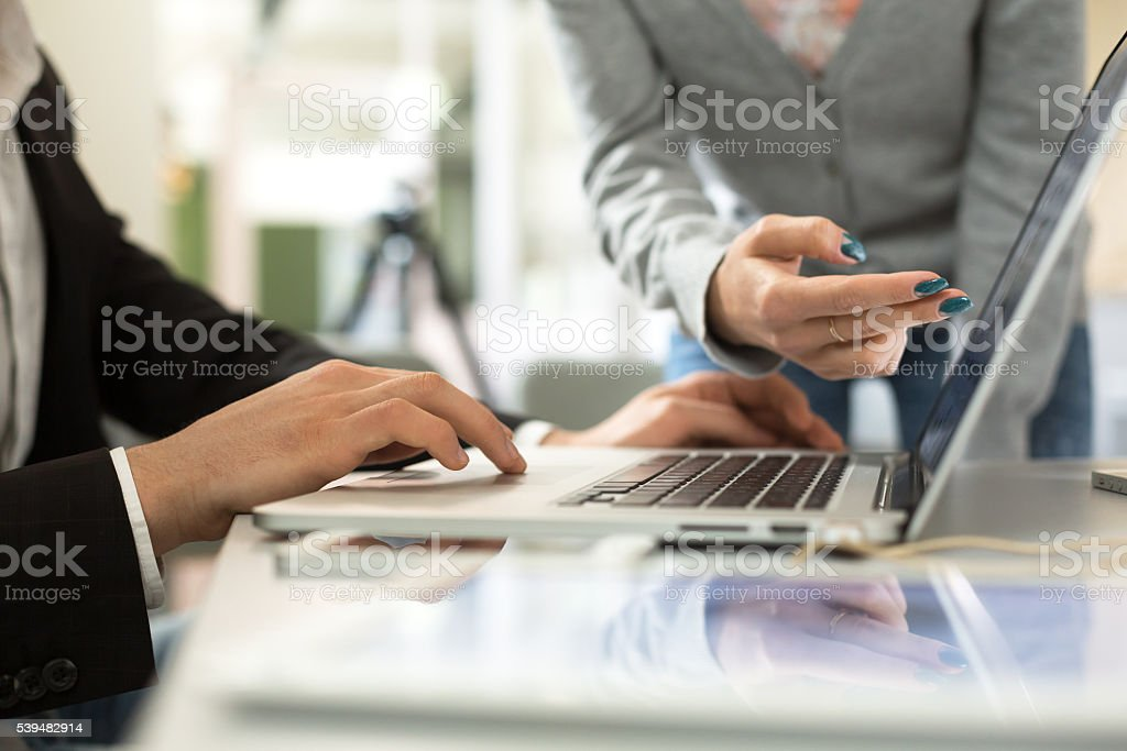 Male and Female Businesspeople discussing Project at Computer stock photo