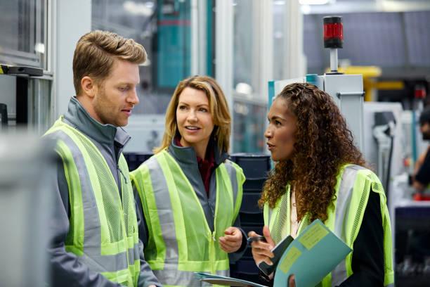 Männliche und weibliche Auto Ingenieure diskutieren über Datei – Foto