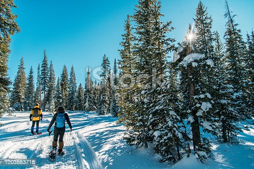 Male and Female Caucasian Adult Hikers Snowshoeing Together on a Groomed Path Outdoors in the Snow