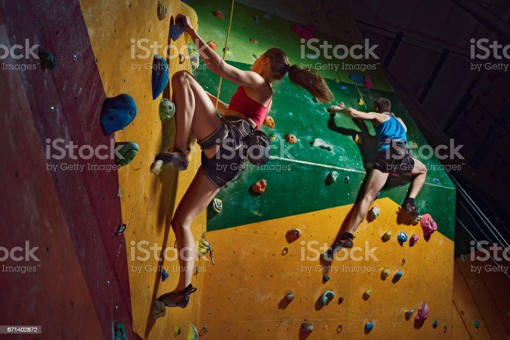 Male and female climbers purposeful climbs up