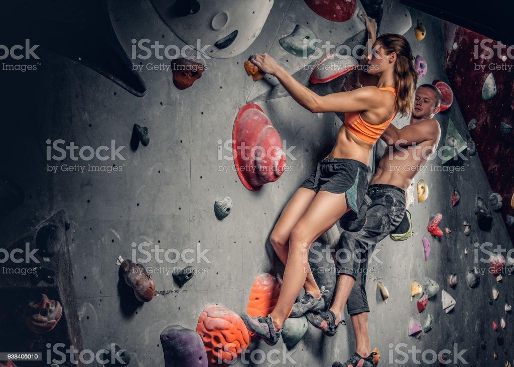 Männliche und weibliche Klettern an einer Kletterwand. – Foto