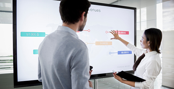 Male and female colleague standing by large screen in meeting room, going over financial presentation shown on screen in meeting room.