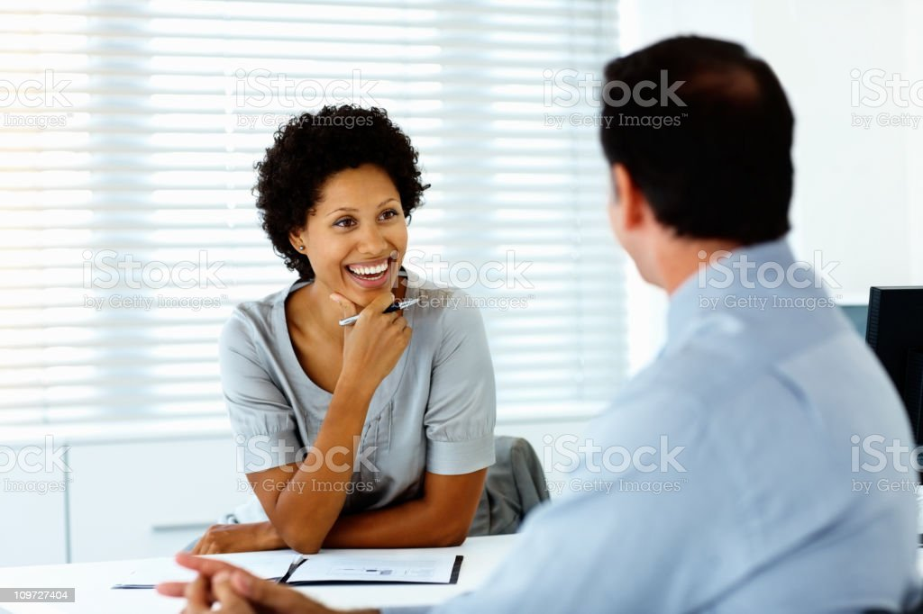 Male and female colleagues discussing in an office setting royalty-free stock photo