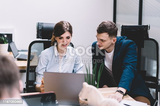 Male and female colleagues watching tutorial on website and discussing working plan on modern laptop device with wireless internet connection.Two IT developers installing app collaborating in office