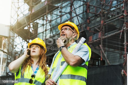 1054724700 istock photo Male and female construction personnel on site looking anxious 1059119434