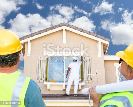 835790922 istock photo Male and Female Contractors Overlooking Painter Painting House 1163418264