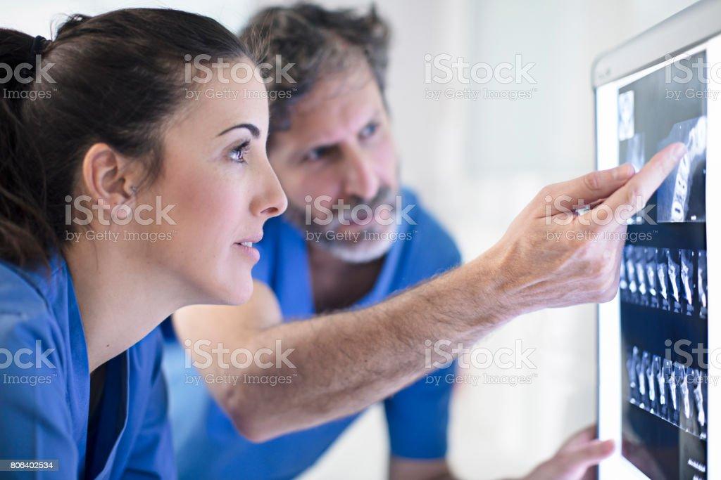 Dentistas masculinos y femeninos, hablar de imagen de rayos x - Foto de stock de 30-34 años libre de derechos