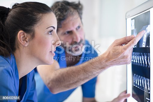 istock Male and female dentists discussing x-ray image 806402534