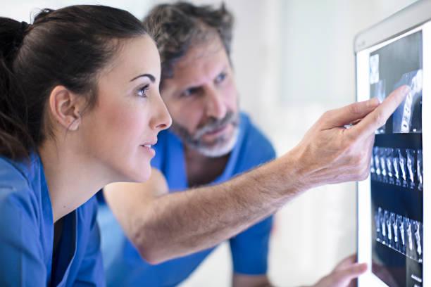 manliga och kvinnliga tandläkare diskuterar röntgenbilden - two dentists talking bildbanksfoton och bilder
