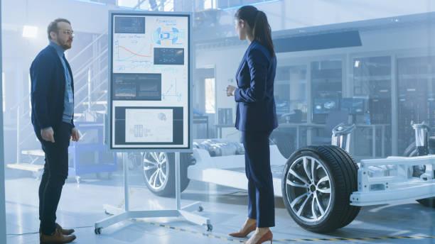 männliche und weibliche design-ingenieure arbeiten und diskutieren die vorteile von elektroautos auf einem interaktiven whiteboard neben einem prototyp eines elektroauto-chassis. high tech laboreinrichtung mit fahrzeugrahmen. - prototype stock-fotos und bilder