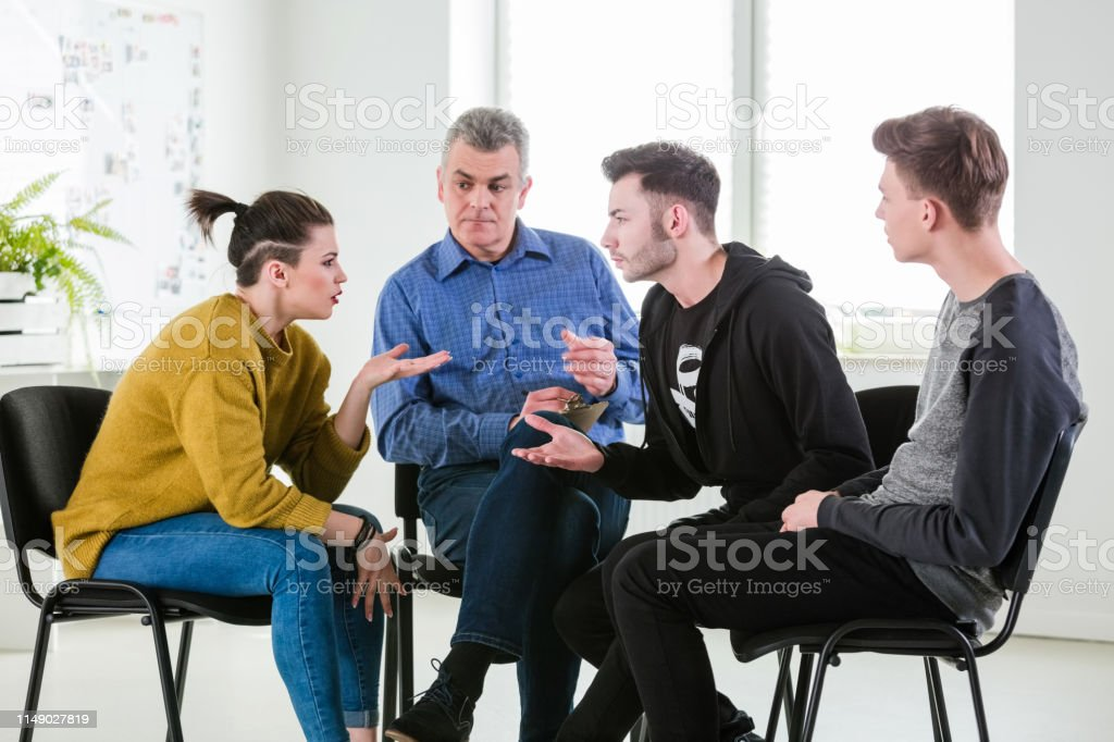Male and female discussing problems during therapy Mature therapist looking at young man and woman discussing problems in lecture hall. Mental health professional is with male and female students. They are in group therapy at university. 18-19 Years Stock Photo