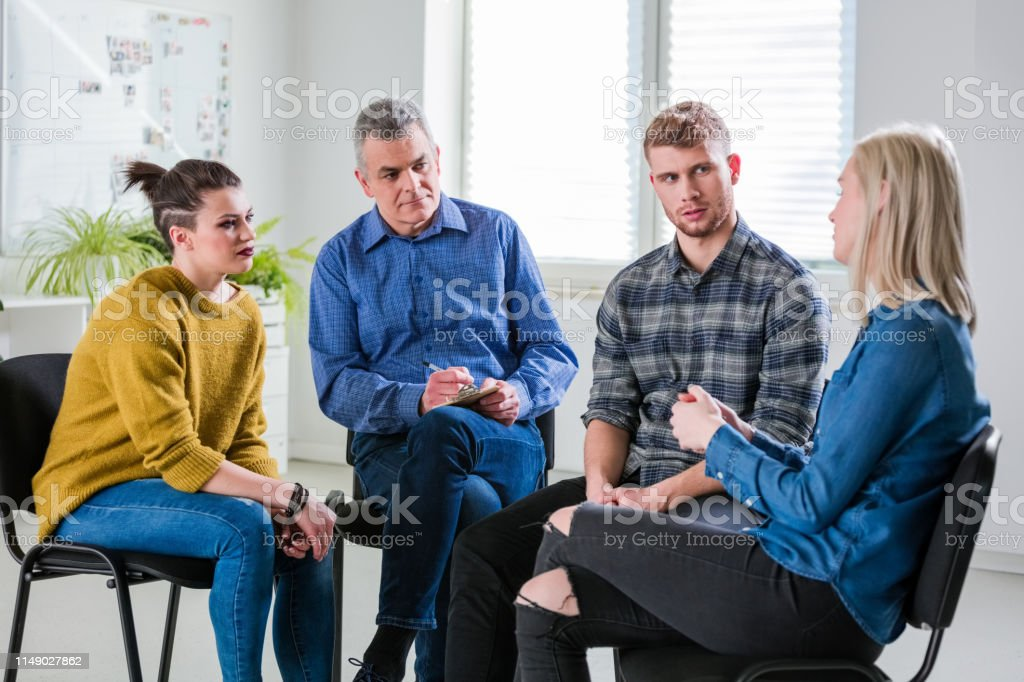Male and female discussing problems during therapy Mature social worker sitting with students discussing problems at lecture hall. Young woman is sharing with friends and therapist at university. They are in group therapy session. 18-19 Years Stock Photo
