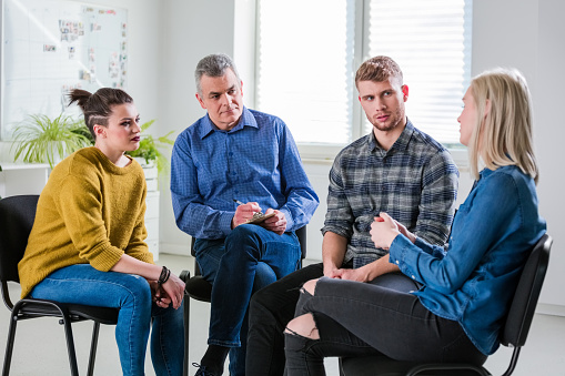 Male And Female Discussing Problems During Therapy Stock Photo - Download Image Now