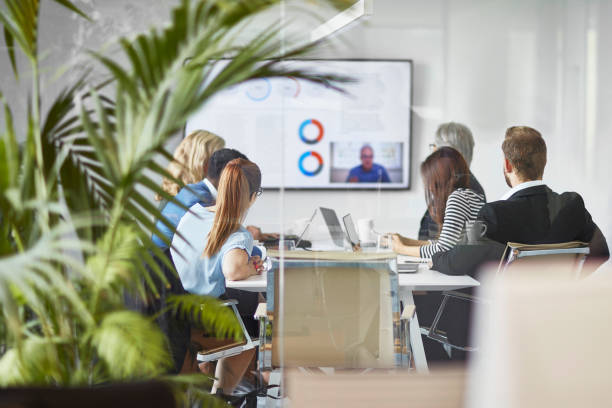 Male and Female Executive Team Video Conferencing with CEO stock photo