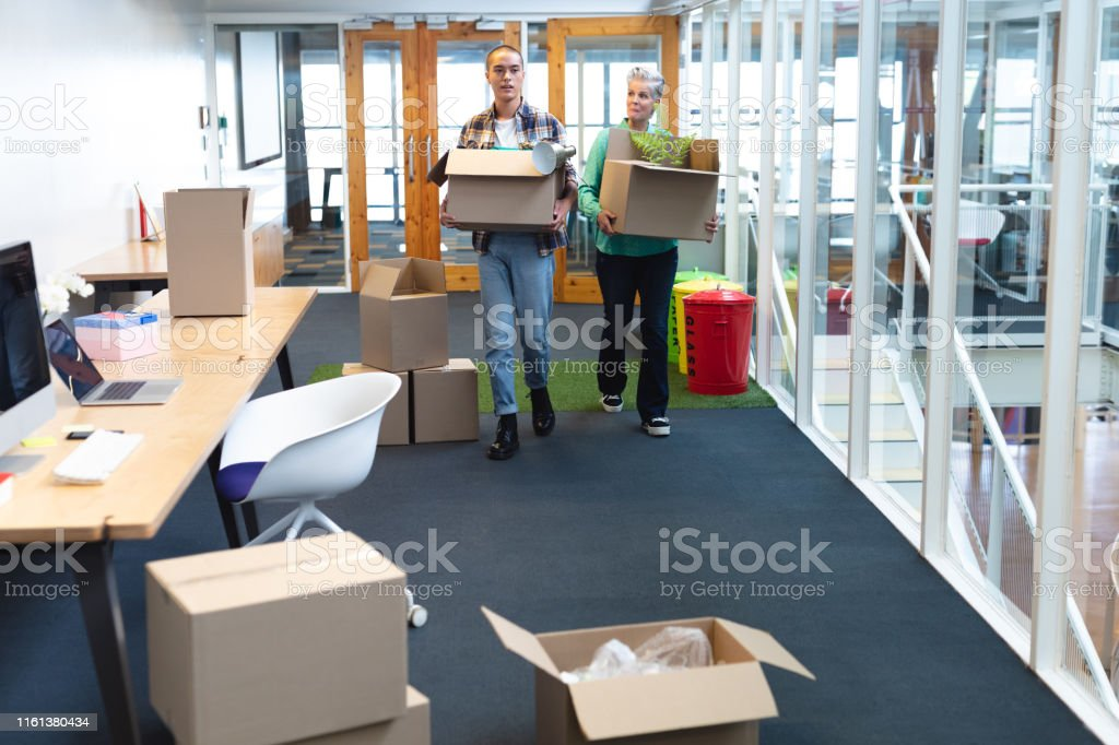 Front view of diverse male and female executives carrying cardboard...