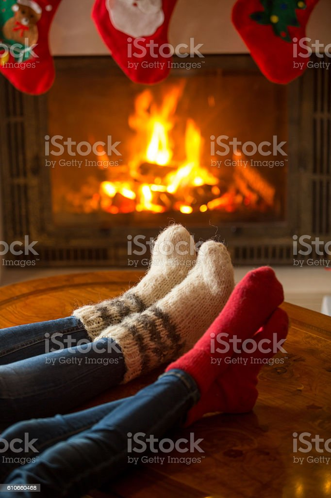 Male and female feet in woolen socks warming at fireplace stock photo