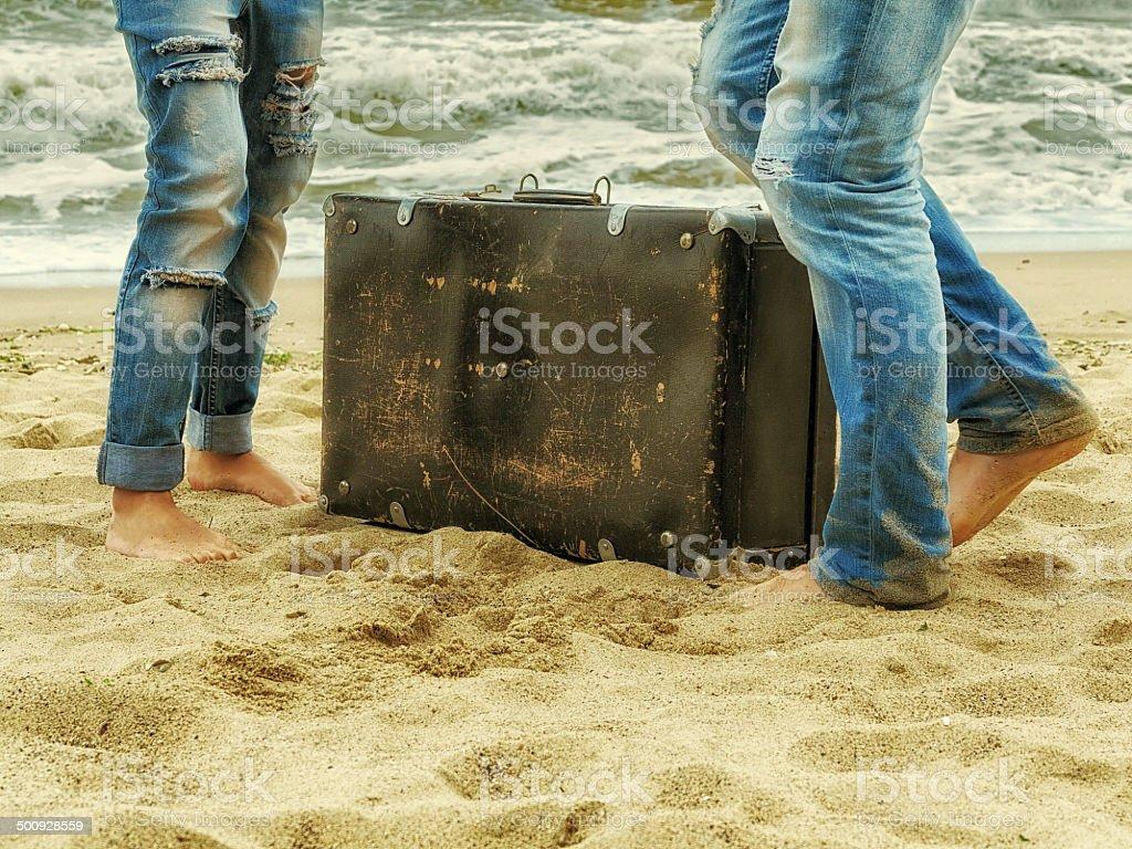 male and female feet on sand near  sea stock photo