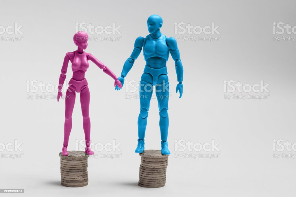 Male and female figurines holding hands and standing on top of equal piles of coins. Income equality concept. stock photo