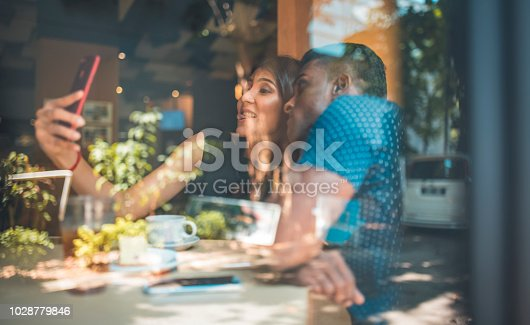 Young man and woman smiling while taking selfie in cafe. Male and female friends are spending weekend together. They are seen through glass window.