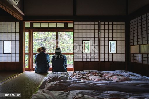 Male and female mixed race guests dressed in yukata enjoying a relaxing stay at a traditional Tokyo ryokan.