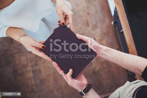 Male and female hands holding a book in a black cover. Relationship, gift.Copy space.