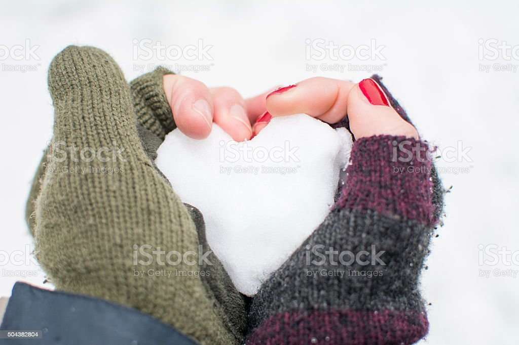 male and female hands  holding a snow shaped heart stock photo