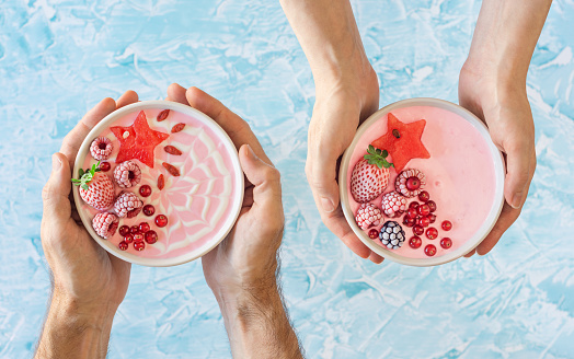 Male and Female Hands Holding Two Pink Berry Yogurt Smoothie Bowls Topped with Fruit