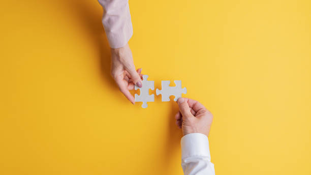 Male and female hands joining two matching puzzle pieces together stock photo