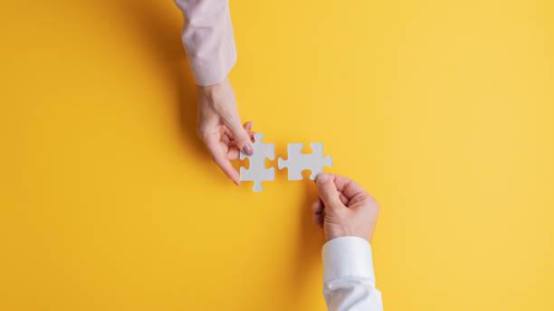 Männliche und weibliche Hände verbinden zwei passende Puzzleteile – Foto