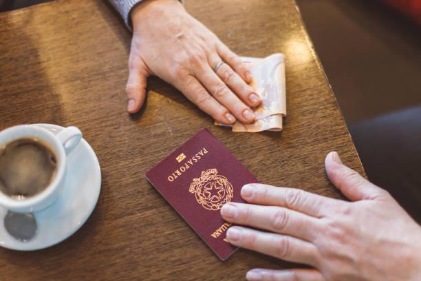 manos masculinas y femeninas con pasaporte y dinero sobre la mesa - concepto de inmigración ilegal, venta de pasaportes falsos, matrimonio falso (falso) - civil rights fotografías e imágenes de stock