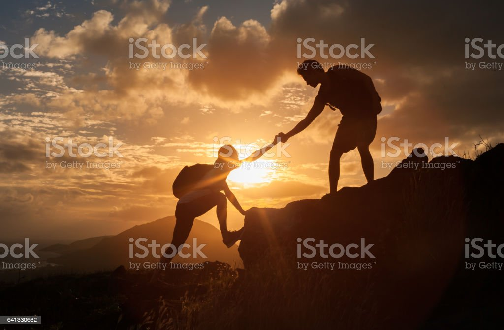 Male and female hikers climbing up mountain cliff and one of them giving helping hand.