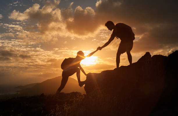 Male and female hikers climbing up mountain cliff and one of them giving helping hand. stock photo