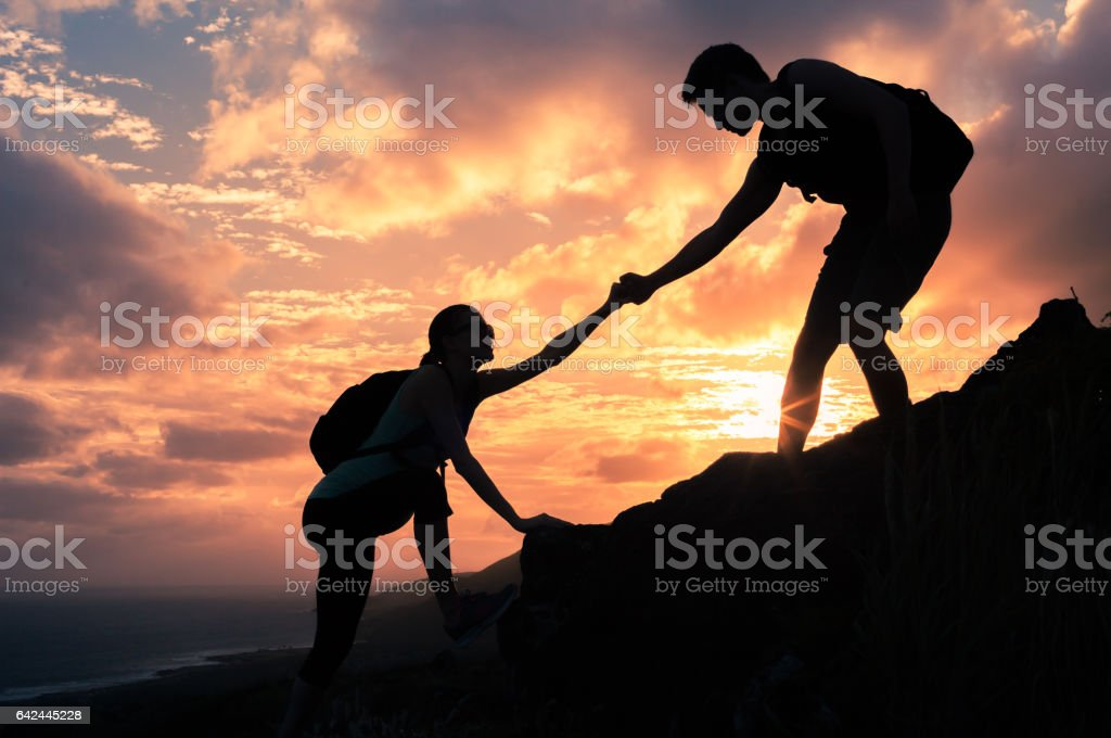 Male and female hikers climbing up mountain cliff and one of them giving helping hand stock photo