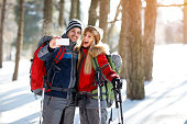 Male and female hikers taking photos on winter holiday in wood