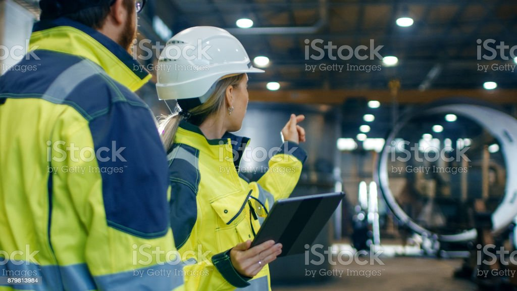 Male and Female Industrial Engineers in Hard Hats and Safety Jackets Discuss New Project while Using Tablet Computer. They Work at the Heavy Industry Manufacturing Factory. stock photo