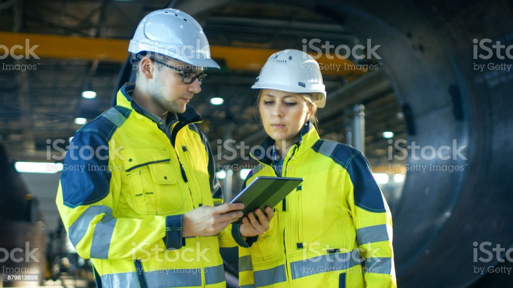 Male and Female Industrial Engineers in Hard Hats Discuss New Project while Using Tablet Computer. They're Making Calculated Engineering Decisions.They Work at the Heavy Industry Manufacturing Factory. Male and Female Industrial Engineers in Hard Hats Discuss New Project while Using Tablet Computer. They're Making Calculated Engineering Decisions.They Work at the Heavy Industry Manufacturing Factory. Adult Stock Photo