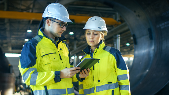 Male And Female Industrial Engineers In Hard Hats Discuss New Project While Using Tablet Computer Theyre Making Calculated Engineering Decisionsthey Work At The Heavy Industry Manufacturing Factory Stock Photo - Download Image Now